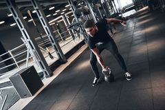 Man fitness. Young strong man during training in the gym stock photography