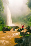 Young strong man traveler enjoy spectacular morning view, beautiful Nungnung Waterfall, Indonesia Stock Photography