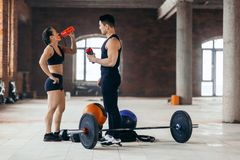 Young strong man and woman drinking water during the training stock image