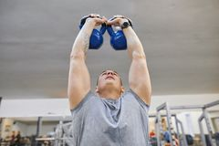 Young strong muscular athlete bodybuilder lifts weights in the gym, weight training.  stock photo