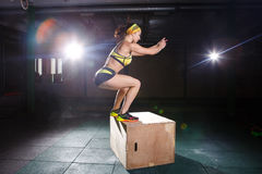 Young, strong muscular girl jumps in the gym to the elevation. Leg training and cardio Stock Photo