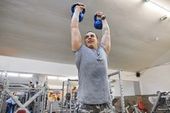 Young strong muscular man in gym lifting heavy free weights.  royalty free stock photo