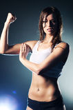 Young strong woman. Showing her muscles stock image
