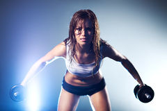 Young strong sexy woman with dumbbells Stock Image