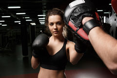 Young strong sports lady boxer standing in gym with man trainer Royalty Free Stock Image