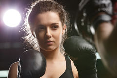 Young strong sports lady boxer standing in gym with man trainer. Photo of concentrated young strong sports lady boxer make exercises in gym with man trainer and stock photography