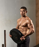 Young strong weightlifter. Portrait of strong muscular man holding bumper plate royalty free stock photo