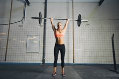 Young strong woman doing weight lifting Royalty Free Stock Image