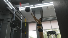 Young strong woman with perfect fitness body in sportswear exercising with medicine ball at gym. Girl doing crossfit. Training. Female athlete squats during stock footage