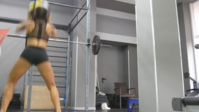 Young strong woman with perfect fitness body in sportswear exercising with medicine ball at gym. Girl doing crossfit stock footage