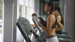 Young strong woman with perfect fitness body in sportswear running on treadmill in gym. Girl exercising during cardio royalty free stock images