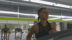 Young strong woman with perfect fitness body in sportswear running on treadmill in gym. Girl exercising during cardio stock video footage