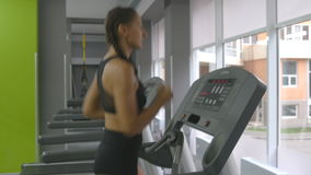 Young strong woman with perfect fitness body in sportswear running on treadmill in gym. Girl exercising during cardio stock video