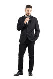 Young stubble man putting black plastic comb inside tuxedo pocket Royalty Free Stock Images