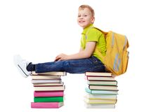 Young student. A smiling boy with satchel sitting on two heaps of books Royalty Free Stock Photos