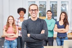 Young student as a self-confident entrepreneur. In front of his start-up team Stock Images