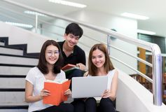 Young Student Asian Group Teenager Reading Book and Using Laptop Computer. Smile in Classroom Education Library at University Knowledge Center Royalty Free Stock Photos