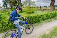 Young student with backpack and bicycle, listening to the music royalty free stock photos