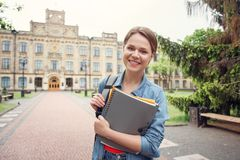 Young student with backpack at university campus walking with notebooks ready for exam smiling playful stock image