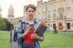 Young student with backpack at university campus walking with notebooks using smartphone concerned stock photo