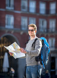 Young student backpacker tourist looking city map in holidays travel Stock Photos