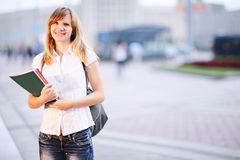Young student, beautiful caucasian woman standing on blurred university building background in the morning. Royalty Free Stock Photos