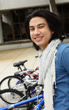Young Student by a Bike Rack. Young student smiling and standing by a bicycle rack at a college Stock Image