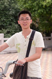 Young Student by a Bike. Young student smiling and standing by a bicycle rack at a park Stock Photography
