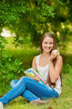 Young student with books and apple. In the park Royalty Free Stock Images