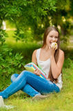 Young student with books and apple. In the park Royalty Free Stock Image