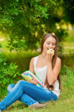 Young student with books and apple. In the park Royalty Free Stock Photo