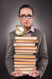 The young student with books and clock Royalty Free Stock Photography