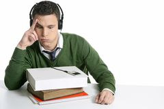 Young student boy with books on desk. Hearing music, over white Stock Image