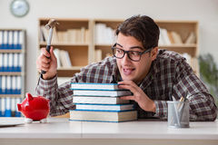 The young student breaking piggy bank to buy textbooks Royalty Free Stock Image