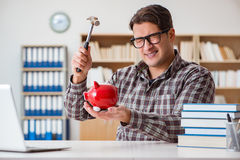 The young student breaking piggy bank to buy textbooks Stock Image