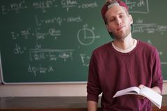 Young student in casual standing near the blackboard with formulas and holding notebook copy space stock photo