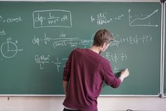 Young student in casual writing physics formula on the blackboard during study course s royalty free stock photo