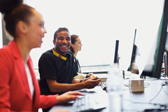 Young student in class with other students working on computers. Young afro american men looking at camera smiling while working on computer in modern classroom Royalty Free Stock Image