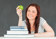 Young student in a classroom looking at an apple Stock Photo