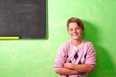 Young student in classroom next to blackboard Royalty Free Stock Photo