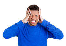 Young student clenching teeth, holding his head having a bad head ache Stock Image
