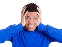 Young student clenching teeth, holding his head having a bad head ache Stock Photos