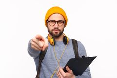 Young student with clipboard pointing at camera. Handsome bearded guy in hat and glasses holding clipboard and pointing at camera isolated on white Stock Photos