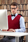 Young  student with  commuter. Smart male  student using computer in library Stock Photo