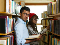 Young student couple choosing books in the library Royalty Free Stock Photography