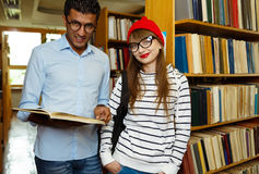 Young student couple choosing books in the library Royalty Free Stock Image