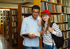 Young student couple choosing books in the library Stock Images