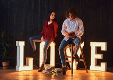 Young student couple reading together in a room decorated with voluminous letters with illumination. stock images