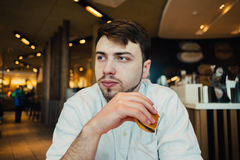 A young student in a cozy restaurant eating fast food burger. Young student with a beard in a cozy restaurant eating fast food burger Royalty Free Stock Photography