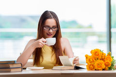 The young student drinking coffee while sudying Stock Photos